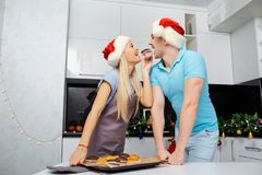 Пара в шляпах Санта Клауса печет пирожные на рождестве в k Стоковые Изображения