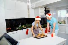 Пара в шляпах Санта Клауса печет пирожные на рождестве в k Стоковое Изображение