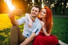 Пара влюбленности делает selfie в парке лета на заходе солнца Стоковое Изображение RF
