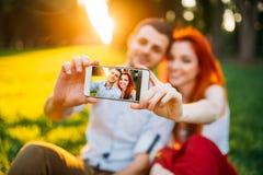 Пара влюбленности делает selfie в парке лета на заходе солнца Стоковые Фотографии RF