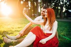 Пара влюбленности делает selfie в парке лета на заходе солнца Стоковое фото RF