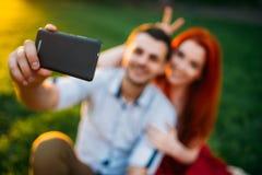 Пара влюбленности делает selfie в парке лета на заходе солнца Стоковая Фотография