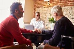 Пара гомосексуалиста мужская держа руки на гостинице проверяет внутри стол Стоковые Фото
