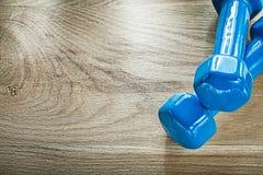 Пара голубых весов гантели на деревянной доске резвится тренируя co Стоковые Фотографии RF