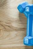Пара голубых гантелей на деревянной доске резвится концепция тренировки Стоковые Фото