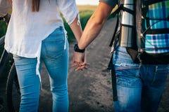 Пара держа руки идет с велосипедами Стоковое Фото