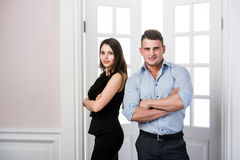 Пара дела стоит совместно и усмехается в офисе просторной квартиры дома входа внутреннем Стоковое Изображение