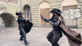 Пара зверских мушкетёров в плащах и шляпах воюет на шпагах, человек впихывает его ногу видеоматериал