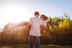 Пара имея человека леса потехи весной держит его подругу в руках и закручивает на заход солнца Парни наслаждаясь жизнью Стоковые Изображения