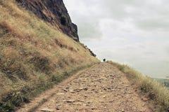Пара идя вверх по месту Артура в Эдинбурге, Шотландии Стоковые Фотографии RF