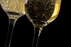 Пара каннелюр шампанского опрокинула с золотыми пузырями Стоковые Изображения