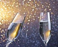 Пара каннелюр шампанского с золотыми пузырями на светлой предпосылке bokeh Стоковые Изображения RF