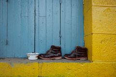 Пара коричневых кожаных ботинок стоит на наклоне желтой стены против предпосылки голубых деревянных закрытых штарок, современного Стоковое фото RF