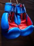 Пара красных и голубых перчаток бокса висит против деревянной стены Стоковое Изображение