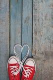 Пара красных ретро тапок на голубой деревянной предпосылке, шнурков Стоковое фото RF