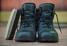 Пара людей чернит ботинки на керамических плитках перед дверью стоковые изображения