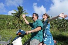 Пара медового месяца ехать мотороллер в тропическом pacific Стоковые Изображения
