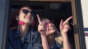 Пара молодых женщин в солнечных очках усмехается в окне трейлера на заходе солнца акции видеоматериалы