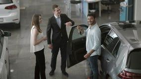 Пара молодые люди покупает автомобиль в выставочном зале автомобиля видеоматериал