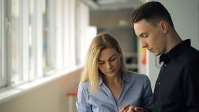 Пара молодых мужчины и женщины работников офиса, обсуждает новое понятие развития компании стоя на окне сток-видео