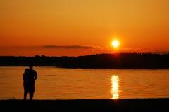 Пара наблюдая заход солнца стоковые фотографии rf