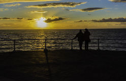 Пара наблюдает заход солнца Стоковое Изображение
