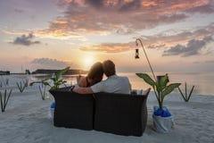 Пара наслаждается событием захода солнца на тропическом пляже Стоковое фото RF