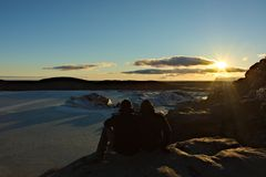 Пара наслаждается заходом солнца над ледником Стоковые Изображения RF