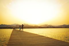 Пара на деревянной пристани на заходе солнца стоковое фото rf