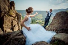 Пара новобрачных отделена и давал руку одина другого Невеста в длинном платье сидит на камне пока Стоковые Изображения