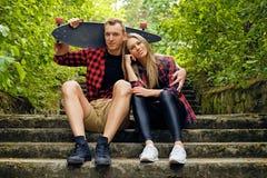 Пара ослабляя на шагах после longboard едет Стоковое Фото
