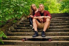 Пара ослабляя на шагах после longboard едет Стоковые Фото