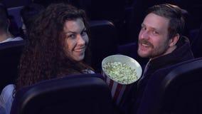 Пара поворачивает их стороны задний на кинотеатре стоковое фото