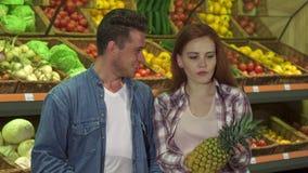 Пара покупает ананас на супермаркете видеоматериал