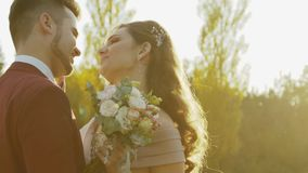 Пара свадьбы ласкает и целует один другого среди мерцаний солнца в дикой степи сток-видео