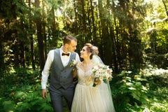 Пара свадьбы наслаждается идти в древесины Новобрачные обнять и придержать руки стоковые фото