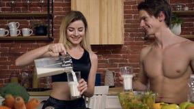 Пара семьи имеет завтрак на уютной кухне, молодая красивая женщина льет молоко ее парень или йогурт в стекле люди видеоматериал