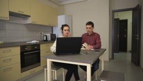 Пара семьи сидит в кухне при компьтер-книжка обсуждая рутинные работы по дому акции видеоматериалы