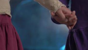 Пара сестер маленьких ребеят в платьях держит руки на голубой предпосылке сток-видео