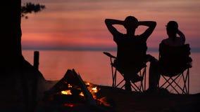 Пара сидит около лагерного костера на ноче видеоматериал