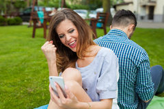Пара сидя на одеяле и gorl использует телефон, она I Стоковые Фотографии RF