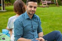 Пара сидя на одеяле и gorl использует телефон Стоковая Фотография RF