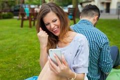 Пара сидя на одеяле и gorl использует телефон Стоковые Изображения RF