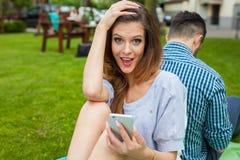 Пара сидя на одеяле и gorl использует телефон Стоковые Фотографии RF