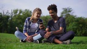 Пара смешанной гонки сидя на траве и выбирает изображения в их smartphone Молодые люди улыбки и смеха мило видеоматериал