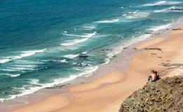 Пара смотрит на пляже Cordoama, Португалии Стоковые Фотографии RF