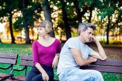 Пара споря пока сидящ на стенде в парке Проблемы в rel стоковое изображение
