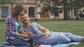 Пара студентов работает на лужайке на кампусе акции видеоматериалы