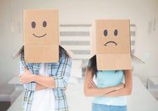 Пара с коробкой возглавляет унылое и счастливое против спальни Стоковое Изображение