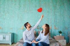Пара с сердцами в их руках сидя на смеяться над кровати Стоковая Фотография RF